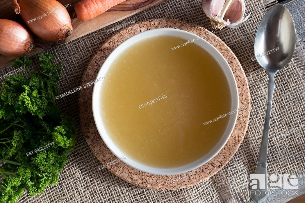 Stock Photo: Chicken bone broth served in a soup bowl, with onions, carrots, parsley and garlic in the background, top view.