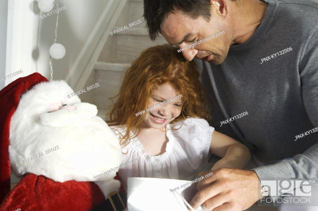 Stock Photo: Father and ldaughter opening Christmas presents, indoors.