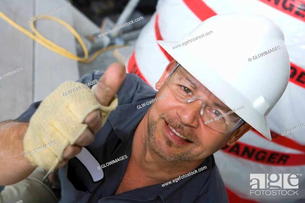 Stock Photo: Portrait of a male construction worker showing a thumbs up sign and smiling.