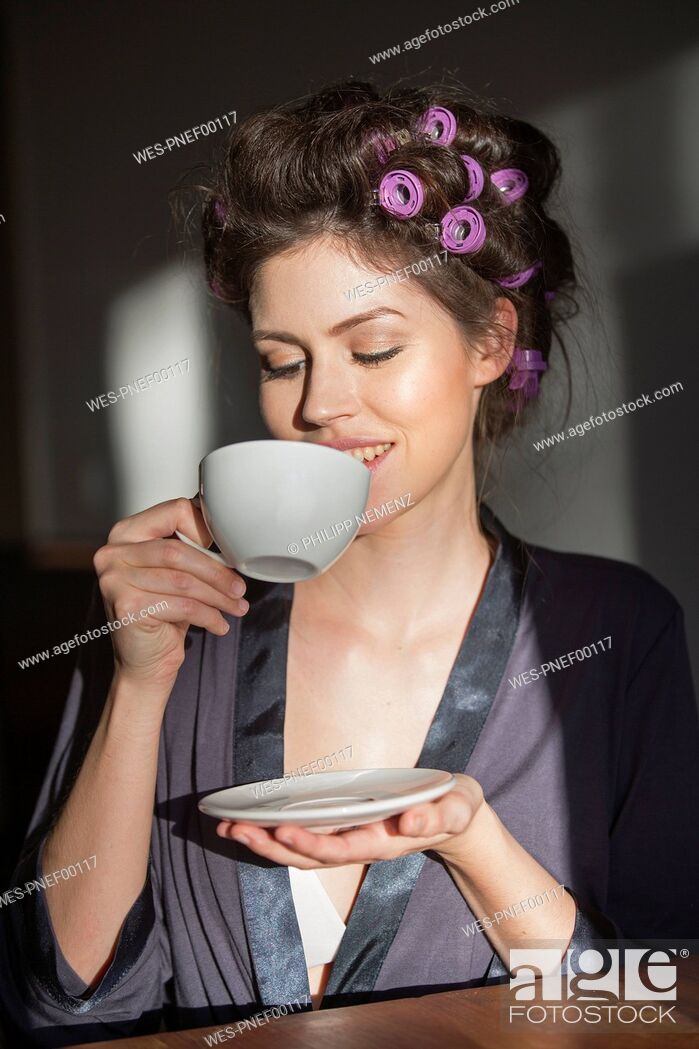 Imagen: Young woman with curlers drinking cup of coffee.