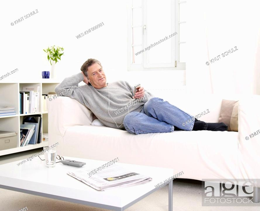 Stock Photo: Germany, Hamburg, Senior man relaxing and listening music.