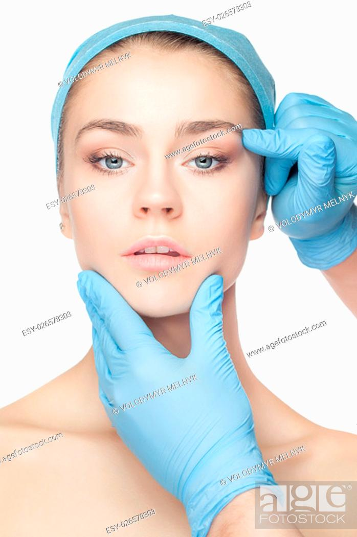 Stock Photo: Plastic surgery concept. Doctor hands in gloves touching the beautiful woman face on white.