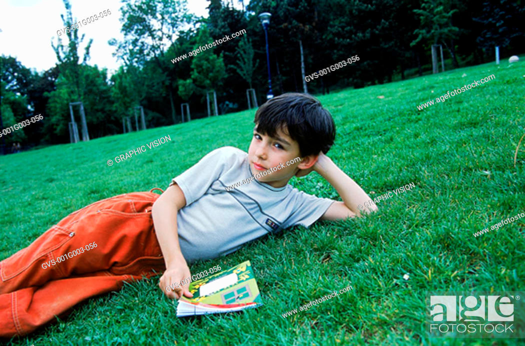 Stock Photo: Young boy lying on the grass holding a book.