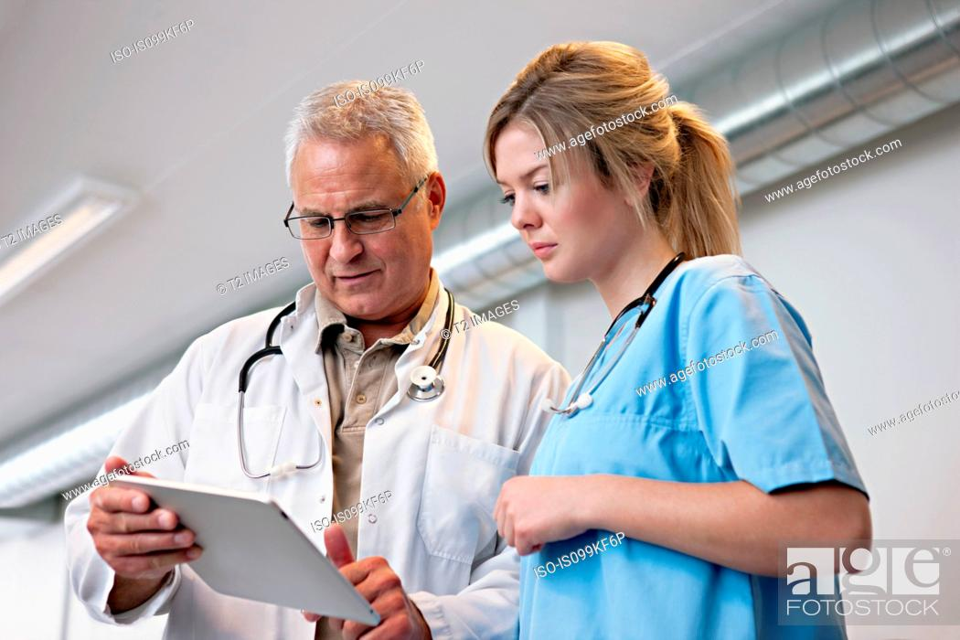 Stock Photo: Doctors looking at digital tablet.