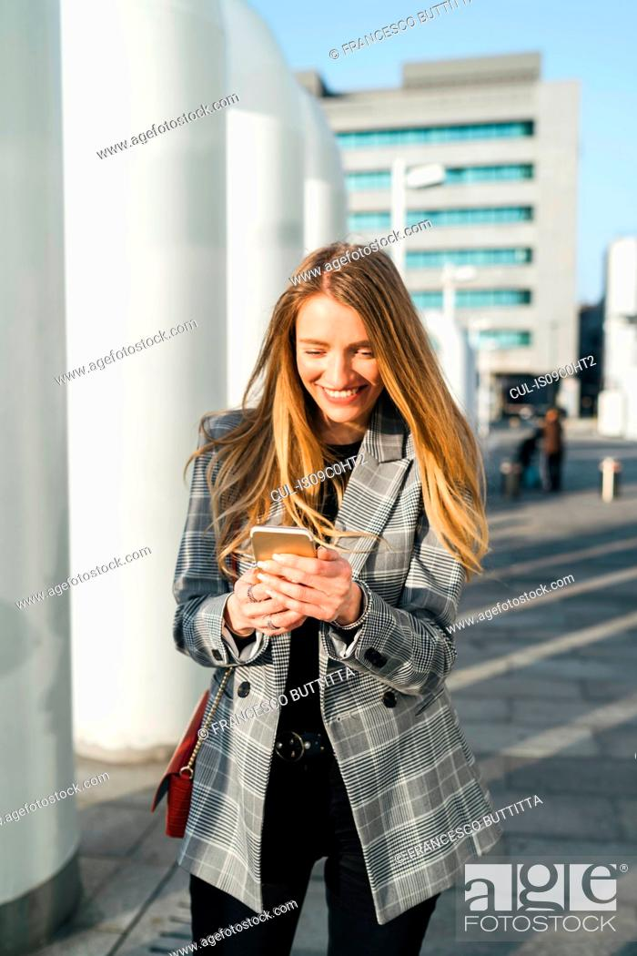 Stock Photo: Young businesswoman with long blond hair looking at smartphone outside office building, Turin, Piemonte, Italy.
