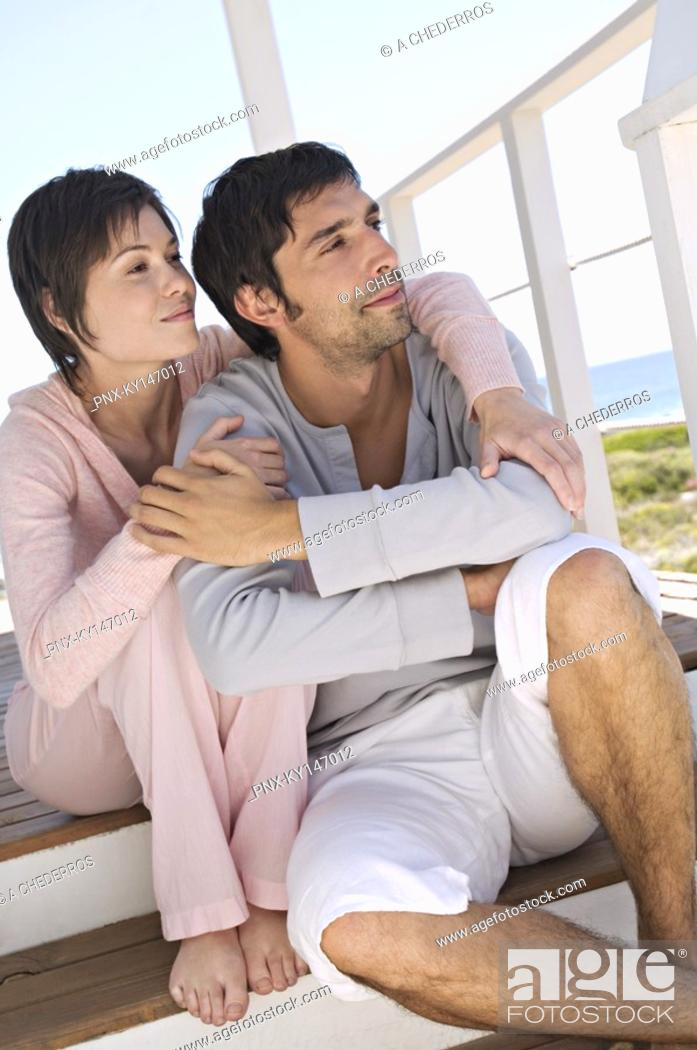 Stock Photo: Couble embracing, sitting on wooden terrace.