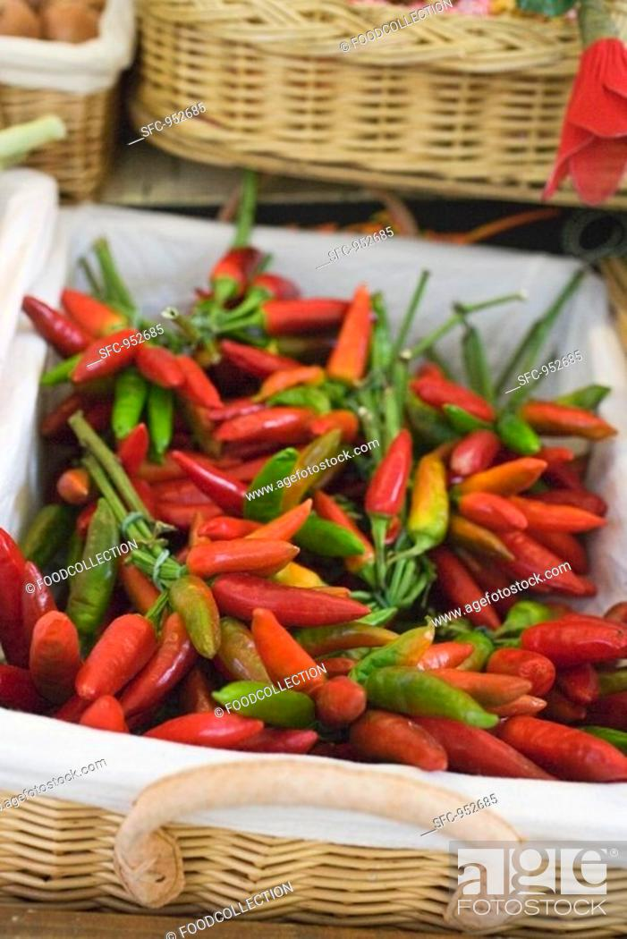 Stock Photo: Fresh chili peppers in a basket at a market.