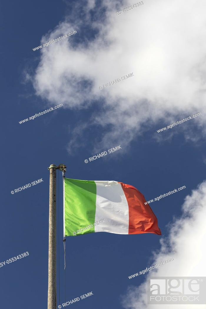 Stock Photo: Italian flag blowing in the wind in the blue sky.