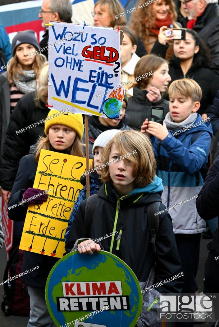 """Stock Photo: 29 November 2019, North Rhine-Westphalia, Cologne: Children hold a demonstration for climate protection with signs saying """"""""Why so much money without a world?""""""""."""