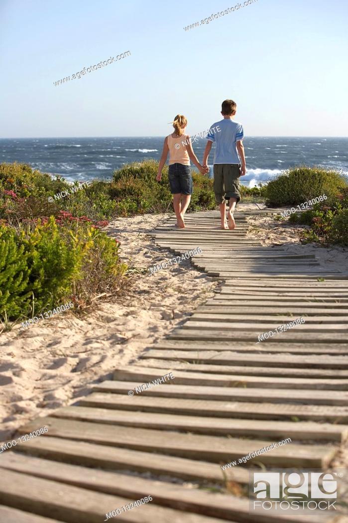 Stock Photo: Boy and girl walking hand in hand along boardwalk toward sea back view.