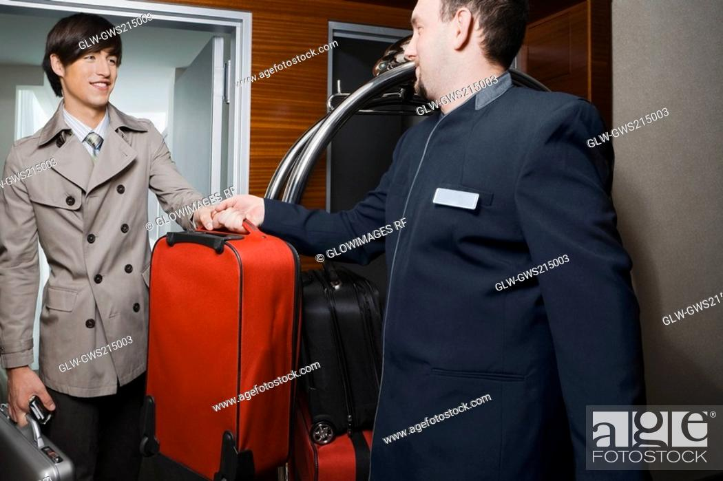 Stock Photo: Room service man handing over luggage to a businessman.