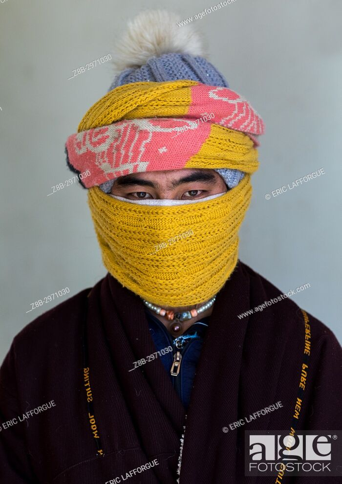 Stock Photo: Portrait of a tibetan nomad man protecting his face from the cold, Qinghai province, Tsekhog, China.