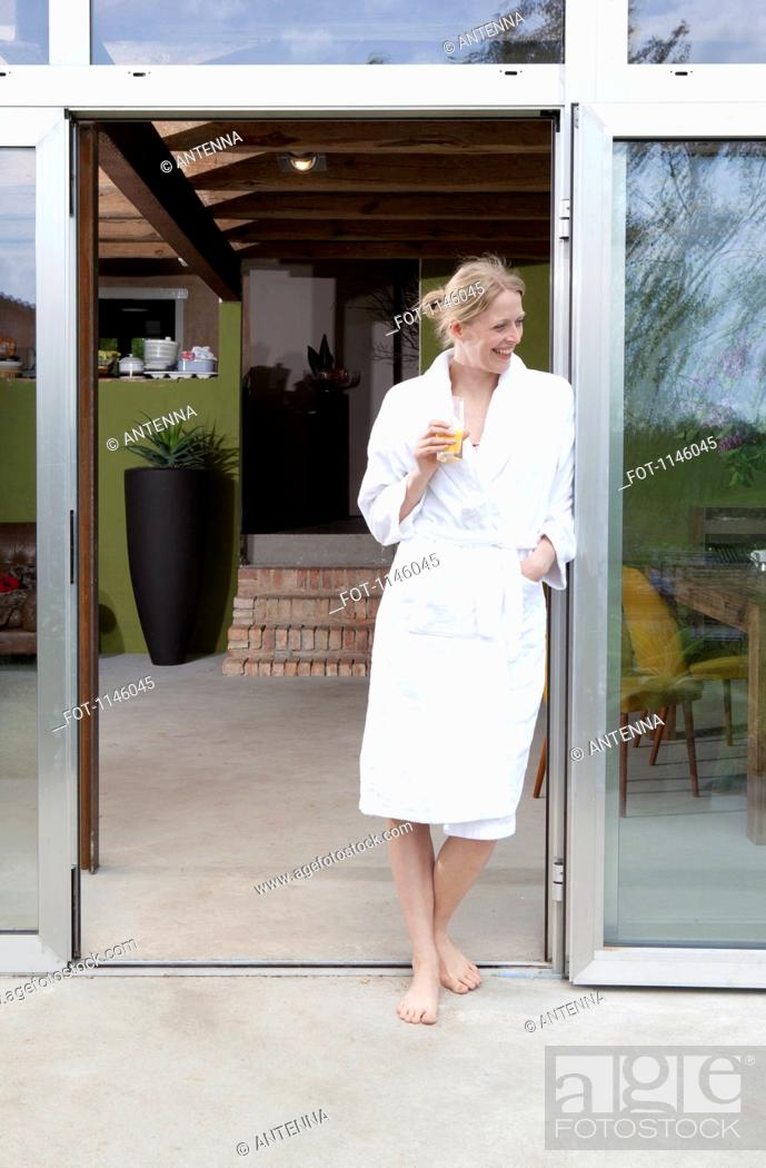 Stock Photo: A happy woman in her bathrobe leaning in the doorway of her house.