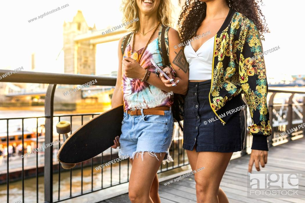 Imagen: UK, London, two friends carrying a longboard with Tower Bridge in background at sunset.