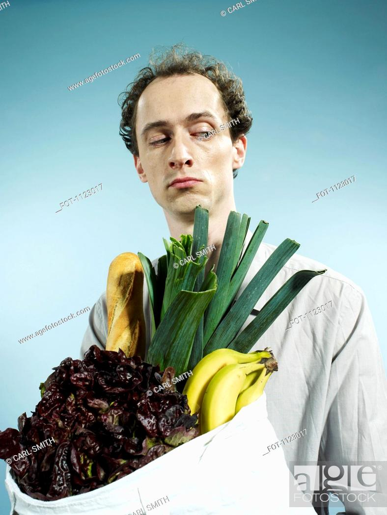 Stock Photo: A man carrying a shopping bag of groceries and looking suspiciously to the side.