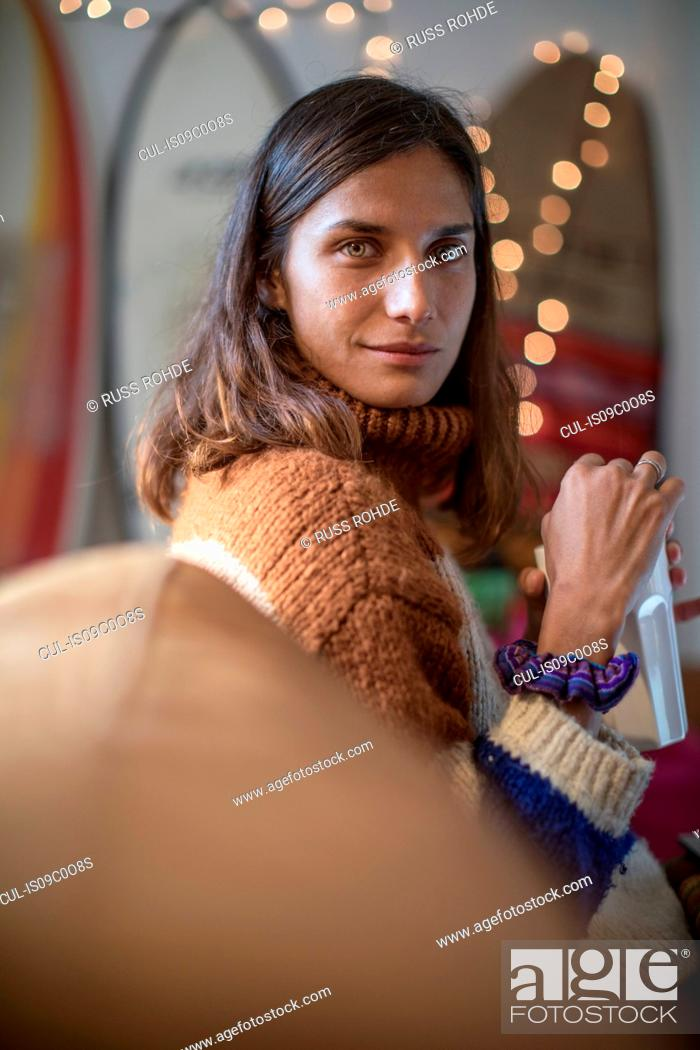 Stock Photo: Young woman in knit sweater relaxing on living room sofa looking over her shoulder, portrait.