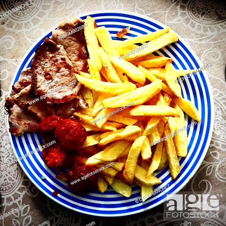 Stock Photo: Fried potatoes, Spanish sausage and Iberian pork meat in a house in Prado del Rey, Sierra de Cadiz, Andalucia, Spain.