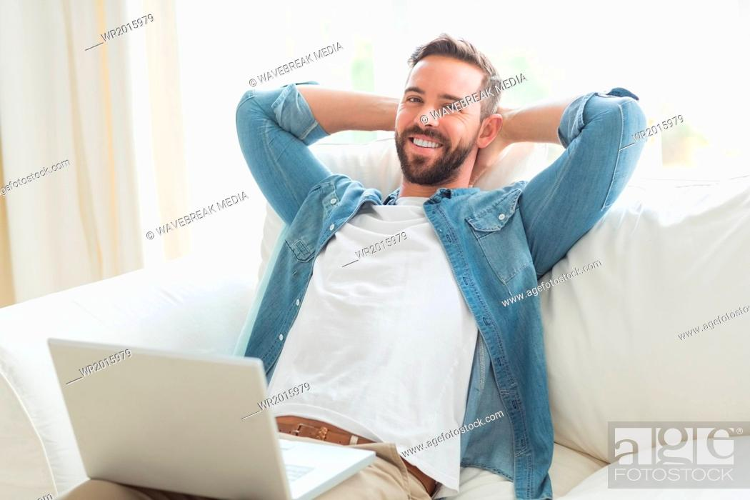 Stock Photo: Smiling man resting in the sofa with laptop beside.