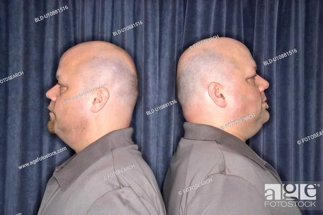 Stock Photo: Profile of bald identical twin mid adult men standing back to back.