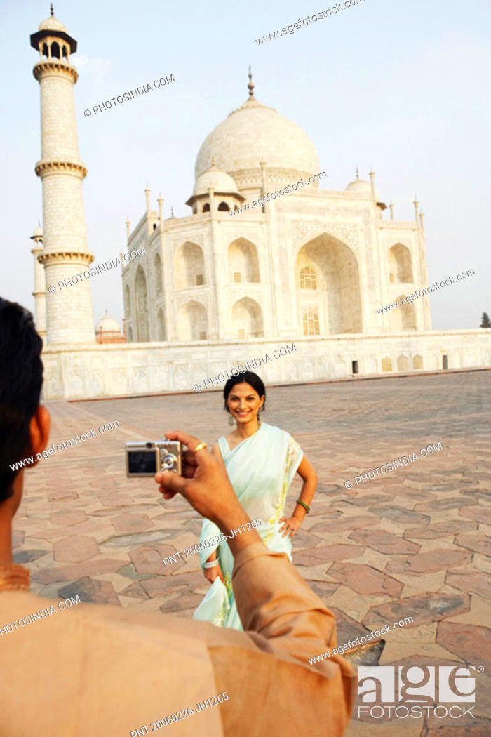 Stock Photo: Rear view of a young man taking a photograph of a young woman in front of a mausoleum, Taj Mahal, Agra, Uttar Pradesh, India.