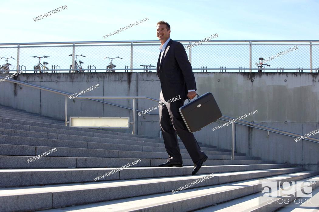 Stock Photo: Germany, Bavaria, Munich, Businessman walking on stairs with briefcase, smiling.
