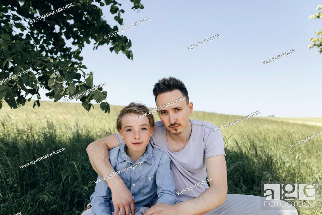 Stock Photo: Portrait of young man embracing boy at a field.