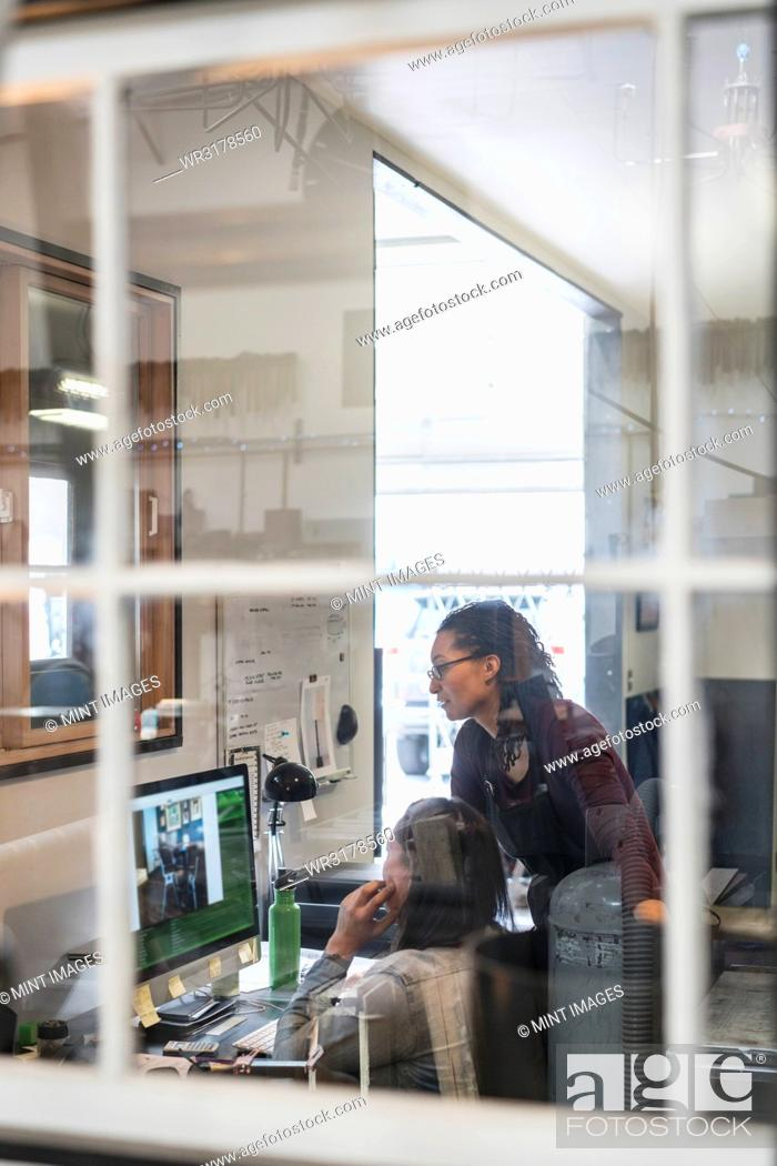 Stock Photo: Two women looking at computer screen in office area of metal workshop.
