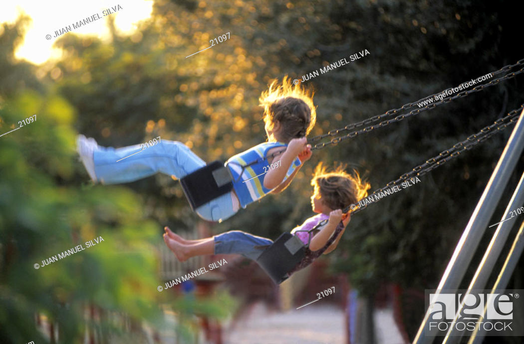 Stock Photo: Girls on a swing in a playground.