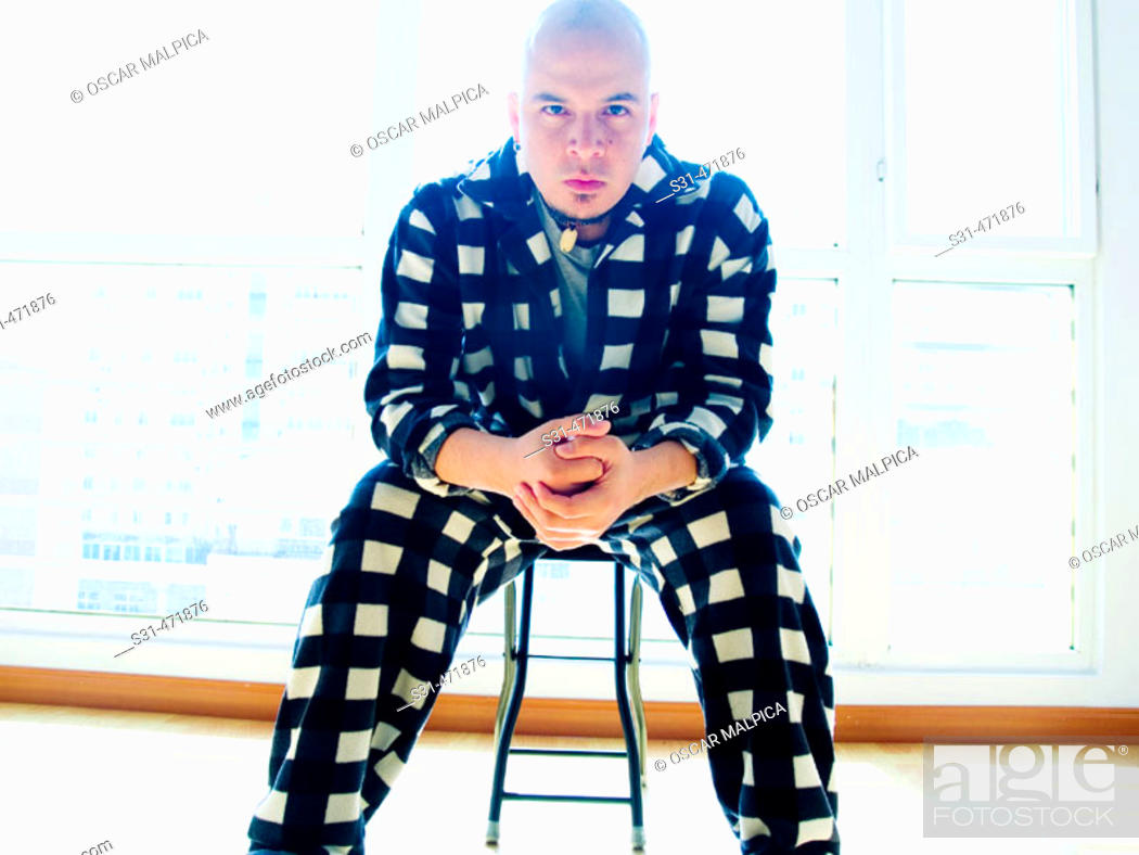 Stock Photo: skinhead male wearing a black and white checked pajamas on a chair looking at the camera.