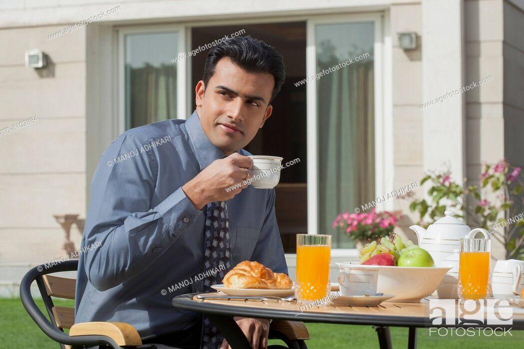 Stock Photo: India, Businessman having breakfast in garden.