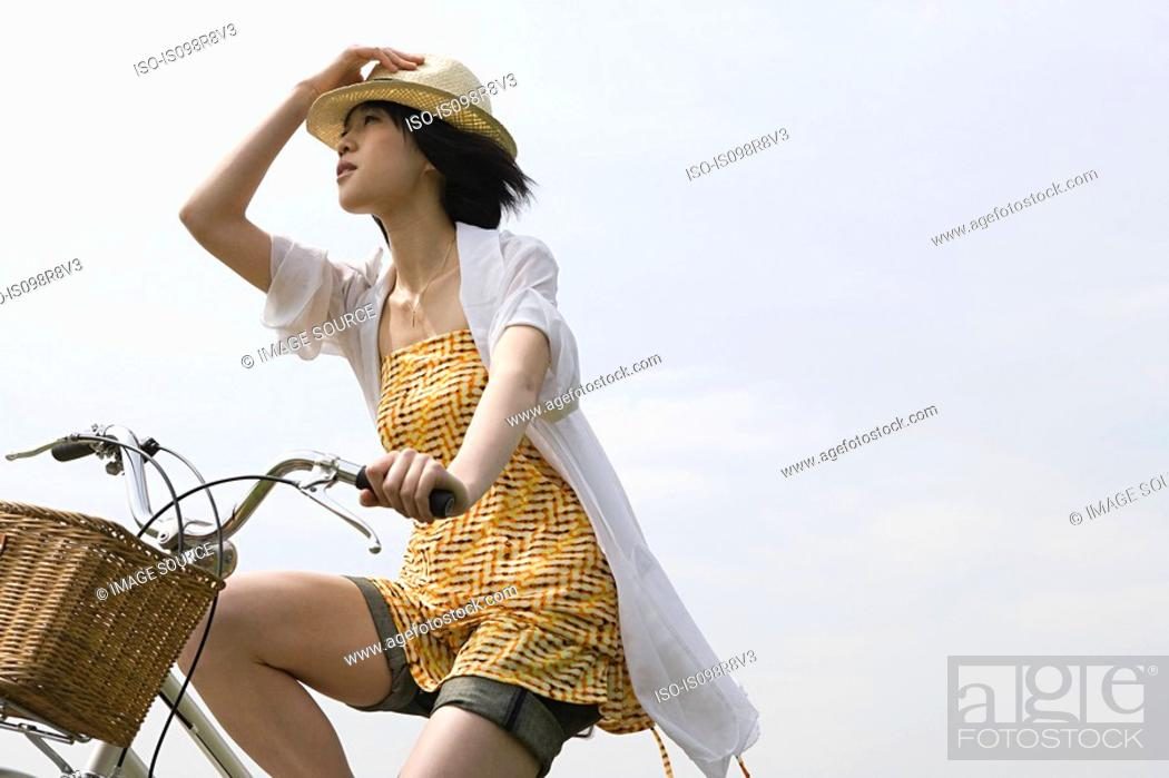 Stock Photo: Young woman cycling.