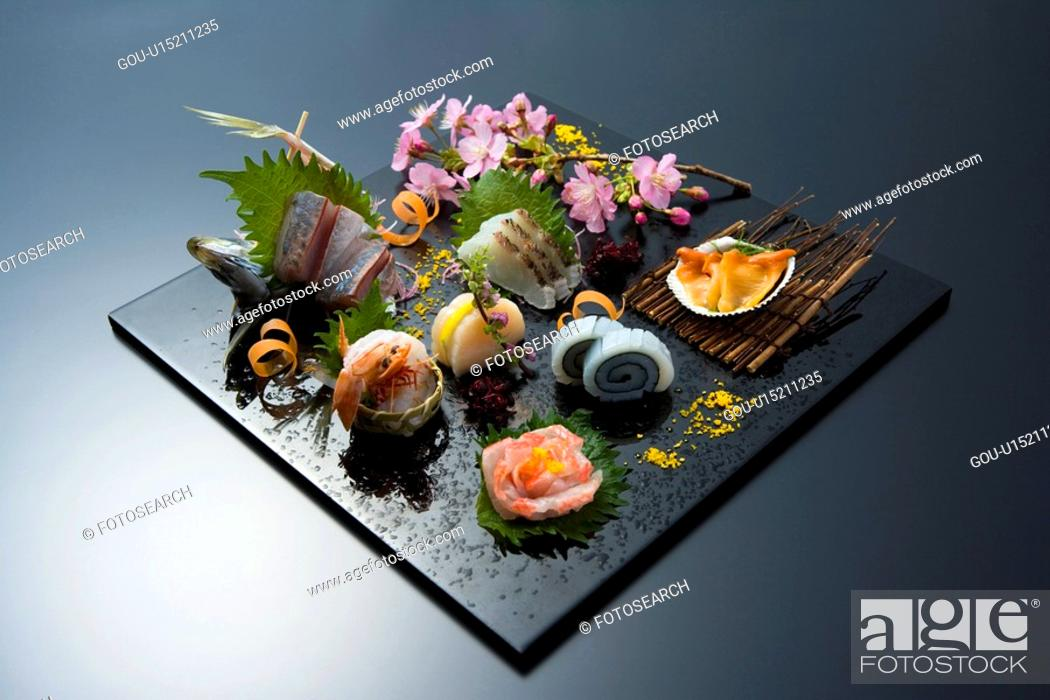 Stock Photo: Sliced raw fishes on a tray, high angle view, black background, Japan.