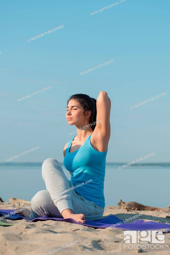 Stock Photo: Woman practicing yoga against a sea background.