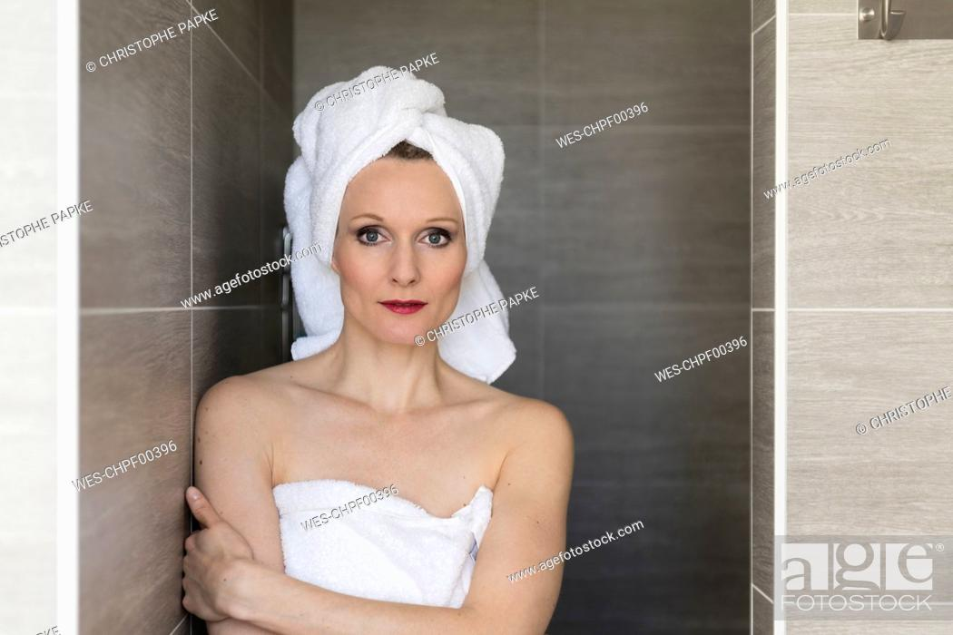 Stock Photo: Portrait of smiling woman wearing towels in the bathroom.