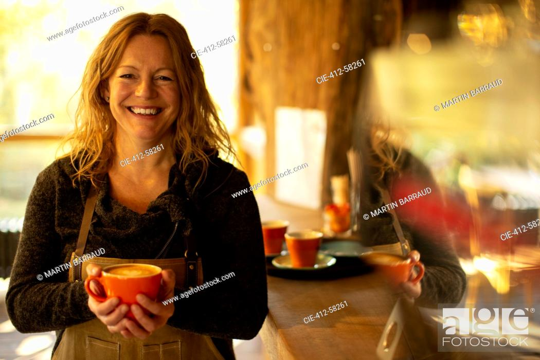 Stock Photo: Portrait happy female coffee shop owner with cappuccino.