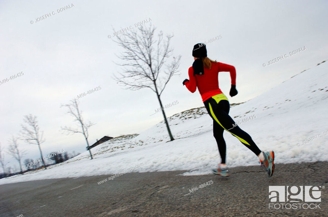 Stock Photo: Female jogger in winter with snow.
