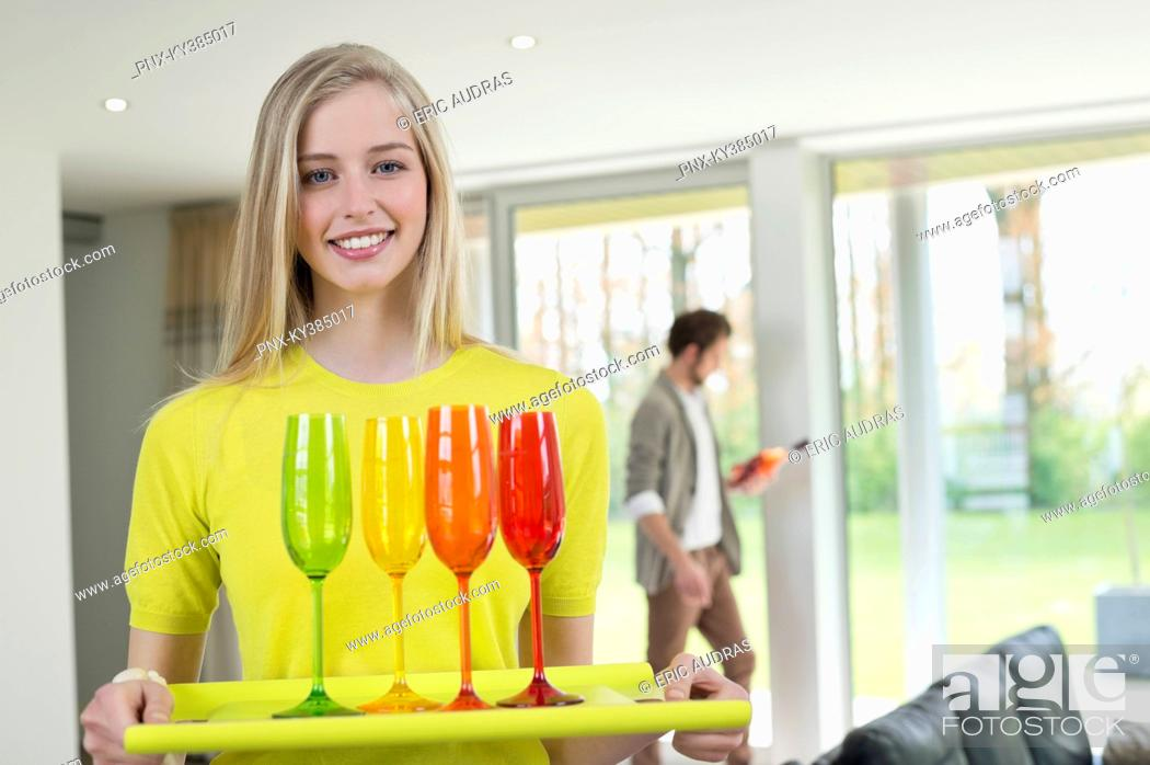 Stock Photo: Happy woman carrying glasses on a tray.