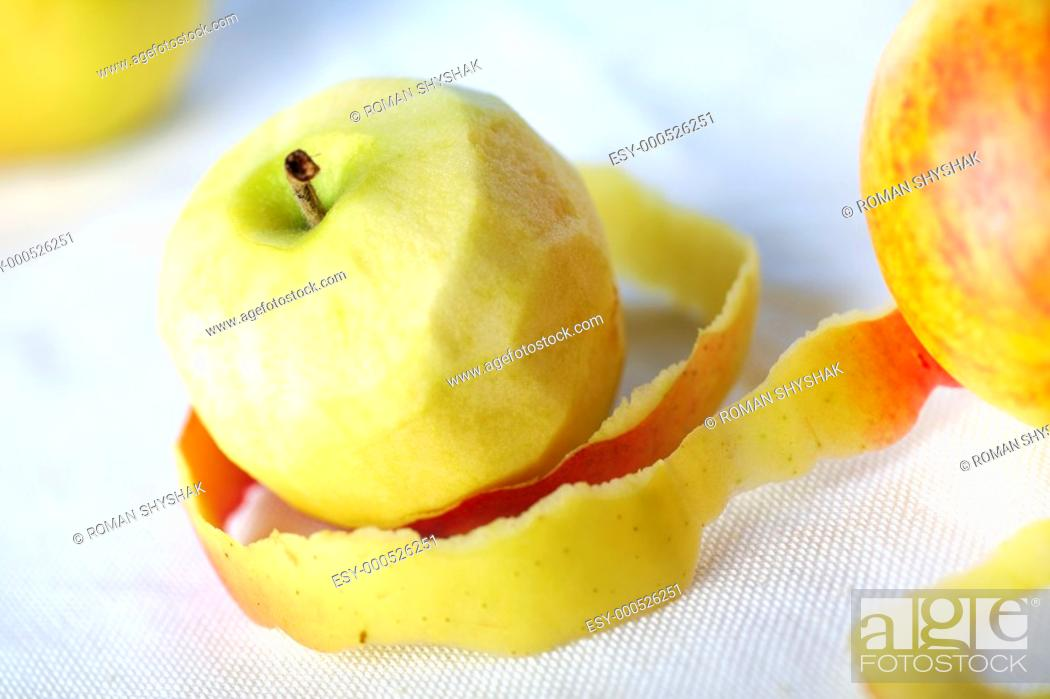 Stock Photo: Yellow apple with peeled twisted skin against other apples.