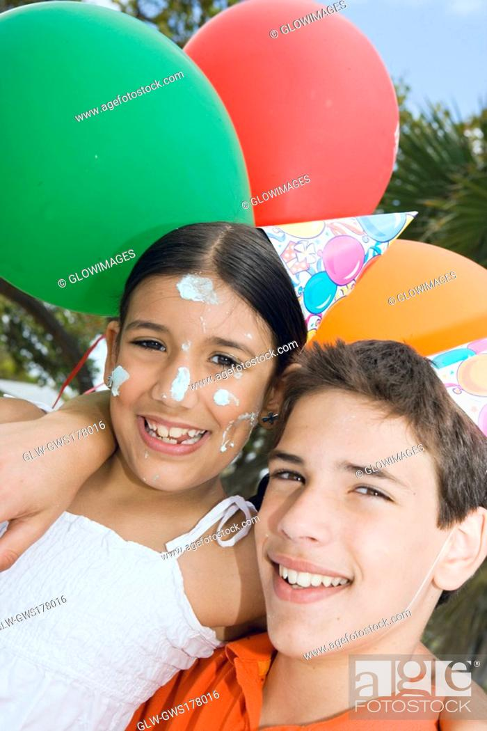 Stock Photo: Portrait of a boy with his sister wearing birthday hats and smiling.
