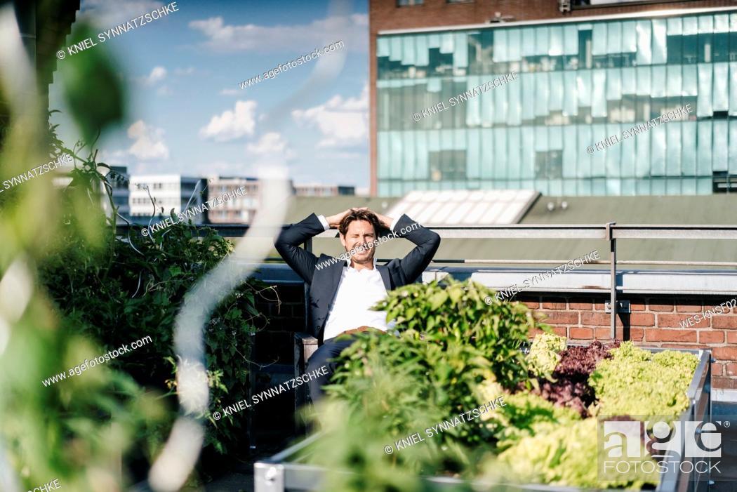 Stock Photo: Businessman relaxing in his urban rooftop garden.