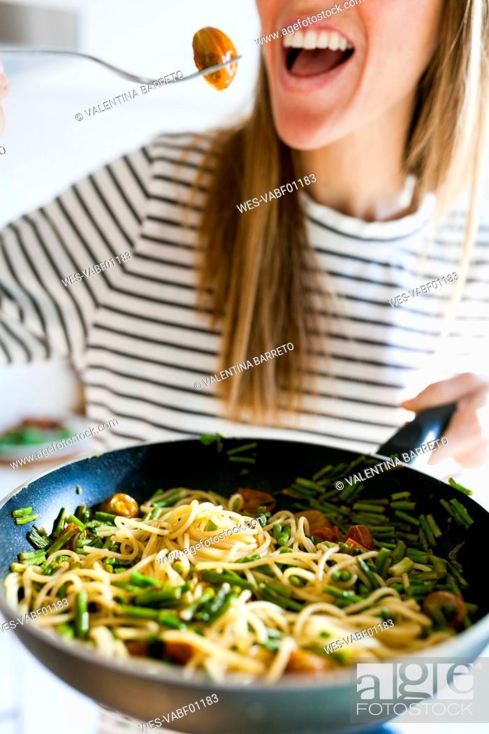 Stock Photo: Young woman holding pan with vegan pasta dish.