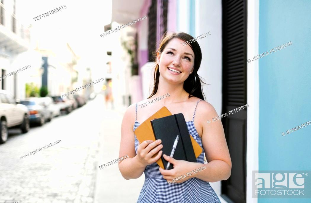 Stock Photo: Puerto Rico, San Juan, Cheerful woman with digital tablet and notebook walking city streets.