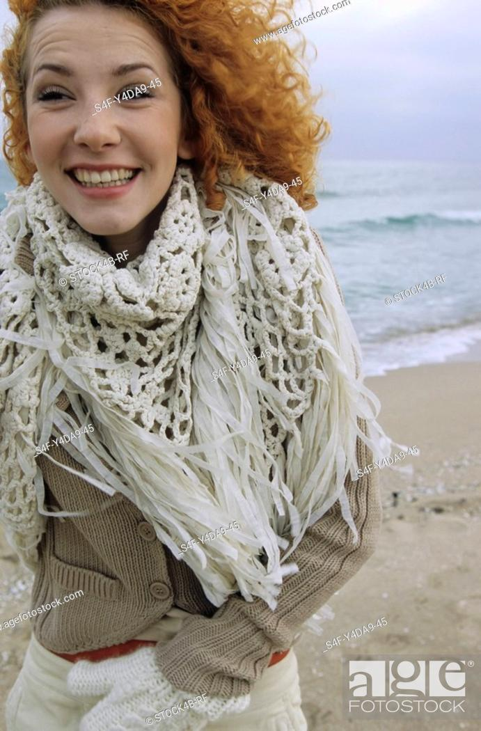 Stock Photo: Young Woman with strawberry-blonde Hair carrying a fringy Scarf around her Neck and is grinning - Fun - Happiness - Beach.