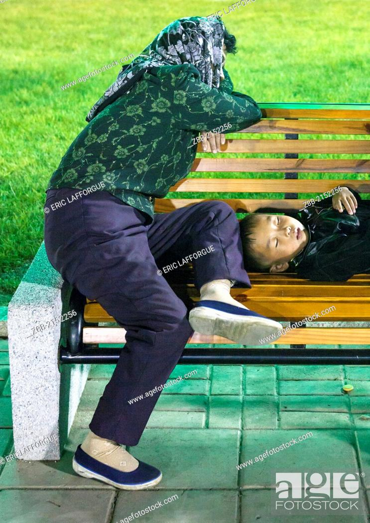 Stock Photo: North Korean Mother And Her Son Sleeping On A Bench At Night, Pyongyang, North Korea.