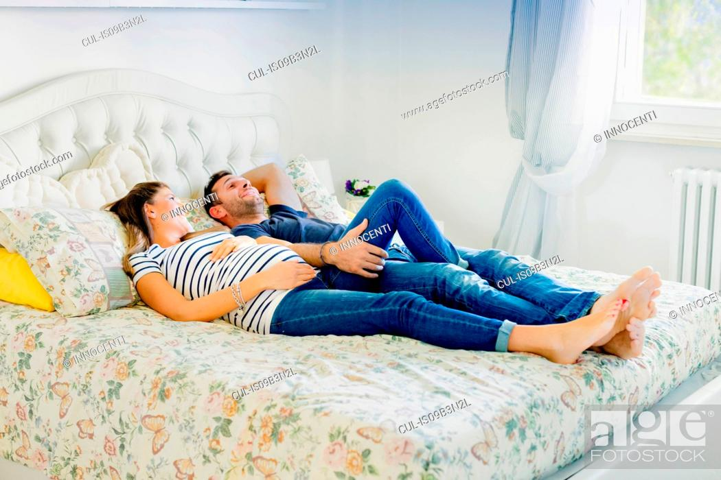 Stock Photo: Pregnant couple lying on bed smiling.