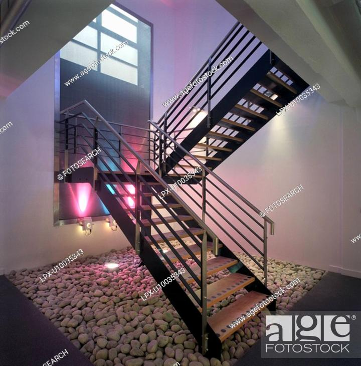 Stock Photo: Modern steel staircase lit by coloured spotlights.