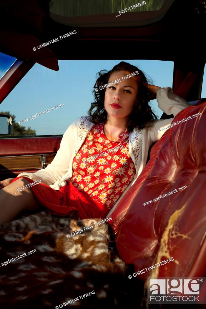 Stock Photo: A pretty rockabilly woman sitting in the passenger seat of a vintage car.