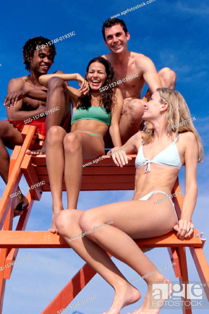 Stock Photo: Low angle view of a group of teenagers sitting on a lifeguard tower.
