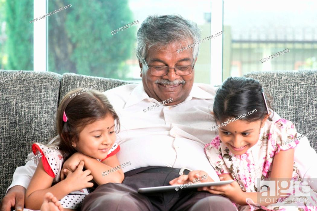 Stock Photo: Modern technology concept. Grandparent and grandchildren using touch screen tablet computer. Portrait Indian family at home.