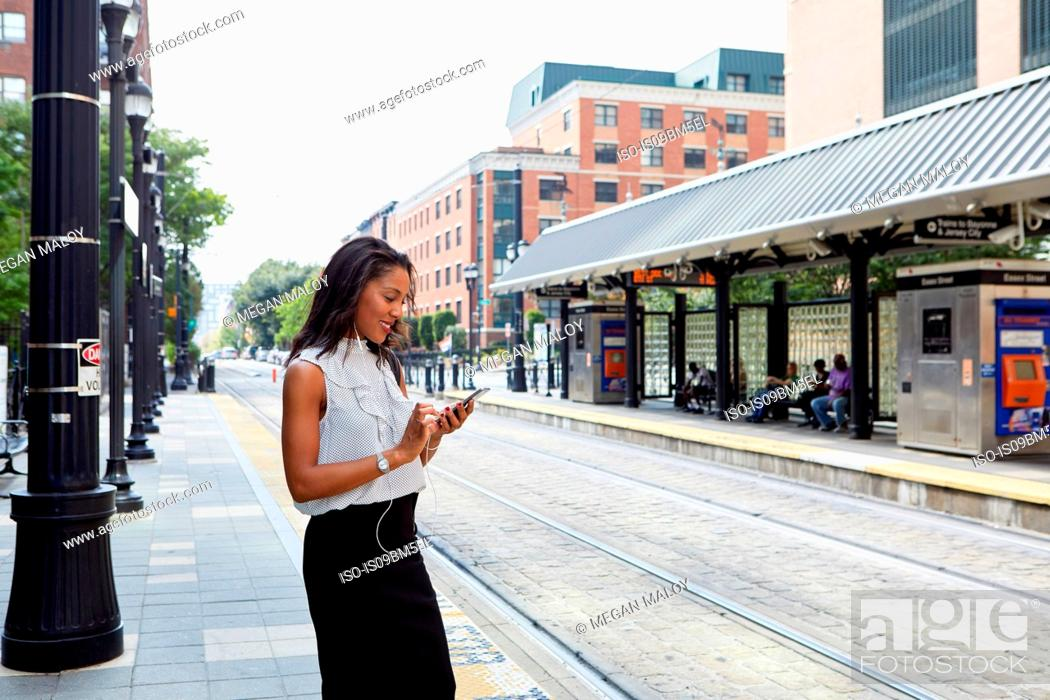 Stock Photo: Businesswoman using cellphone in light rail station.